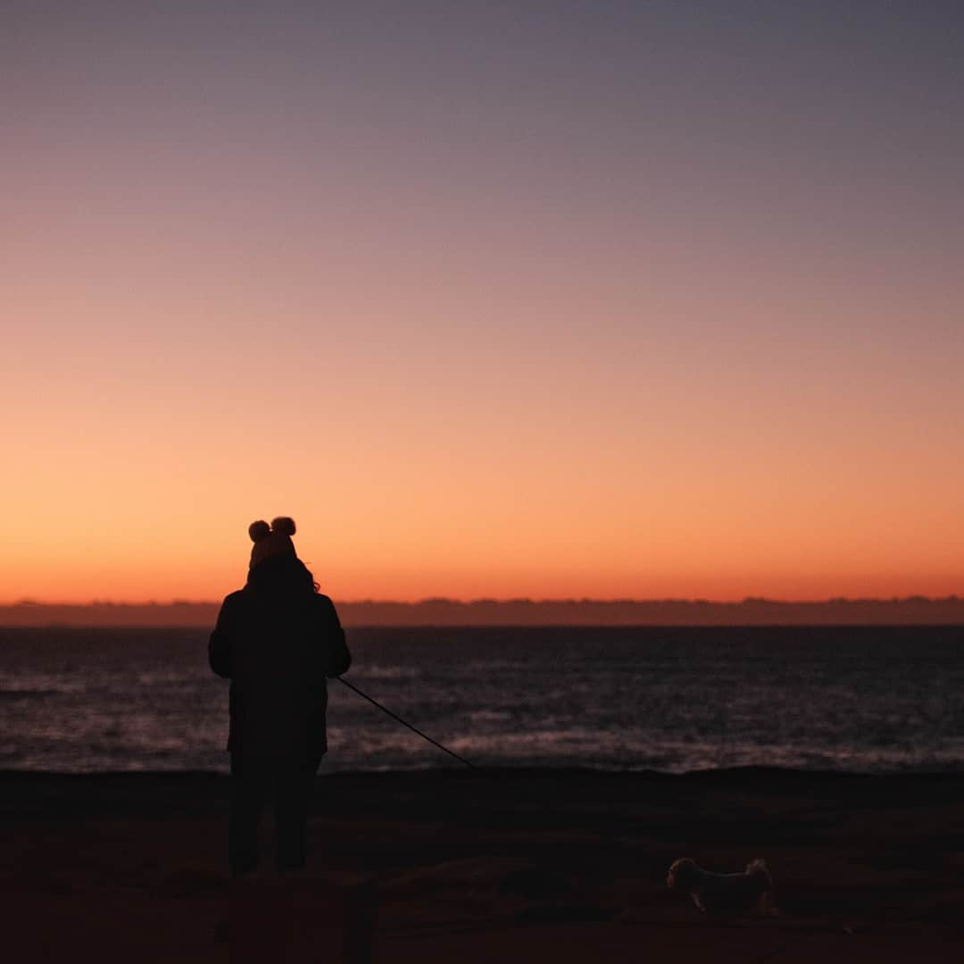 A man standing in front of a sunset