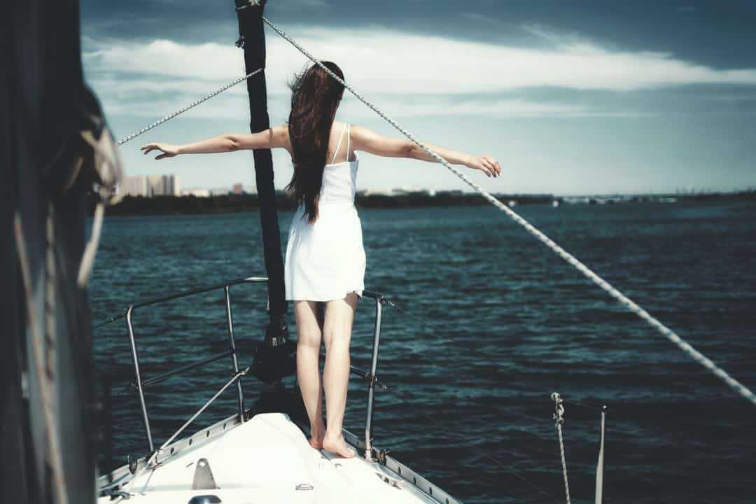 A person standing in front of a boat next to a body of water